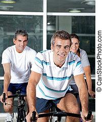 People On Spinning Bike In Health Club