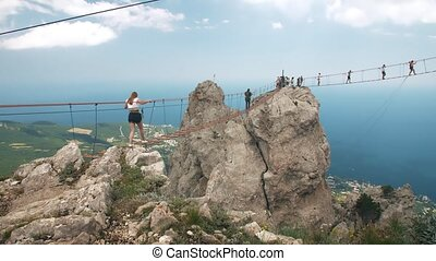 People on suspension bridge - Group of people walking by...