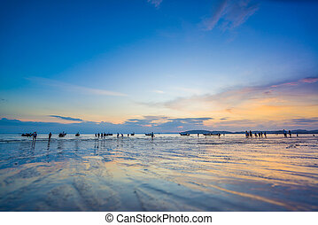 People on the Ao Nang beach at sunset in Krabi