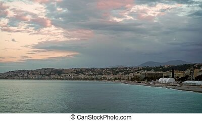 People on the beach of Nice, France at sunrise
