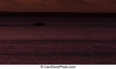People on the beach on silhouette with boats