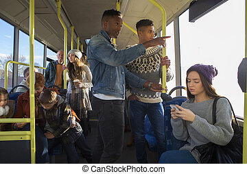 People on the bus - Two men are standing on a bus. There are...