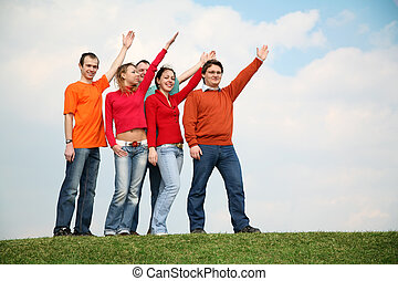 people on the grass with the raised hands