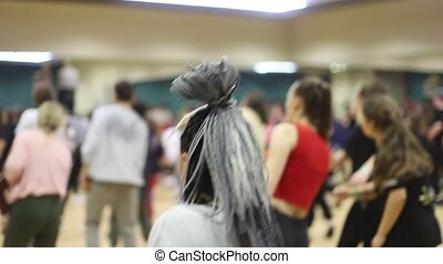 People on the open lesson indoors. A lot of people on dancing class. A woman with grey african braids