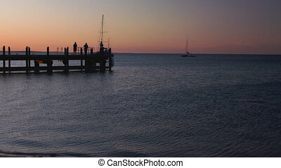 People on the pier on silhouette - A full shot of silhouette...