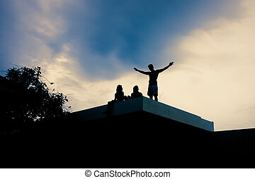 People on the roof of a house at sundown