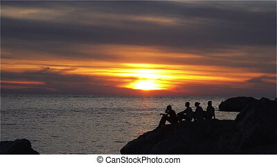 People on the Shore at Sunset