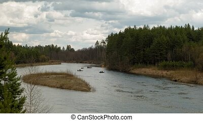 People paddle along the river in cloudy weather. A beautiful...