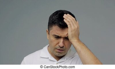 unhappy man suffering from head ache - people, pain and...