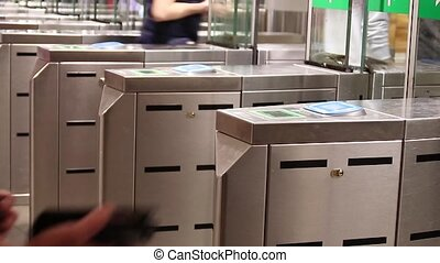 People pass through the turnstiles in the subway in rush hour. Payment system in the underground transport. Passengers pay the fare.