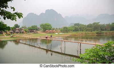 people passing bamboo bridge on limestone mountain background