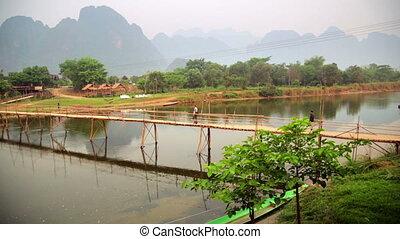 people passing bamboo bridge on limestone mountain...