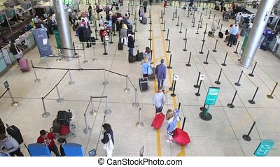 People passing check-in desks in Dublin Airport, Ireland.