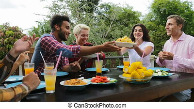 People Passing Food Eating On Terrace Young Friends Talking Sitting At Table Outdoors Communication