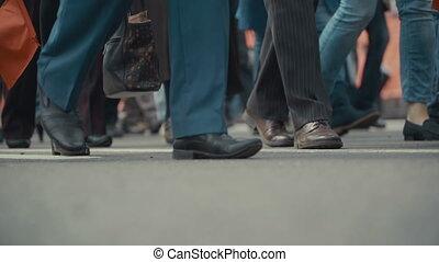 People pedestrians walks across a busy city street.