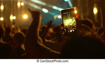People use smart phones video at music concert
