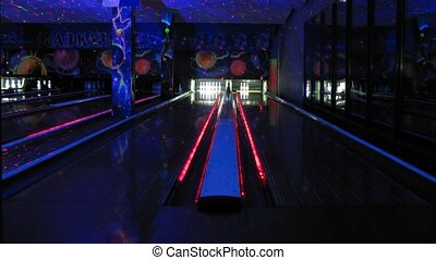 People play bowling in dark club, time lapse