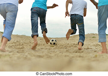 People playing football on a beach