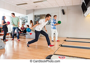 People Playing in Bowling Alley - Group of young people...