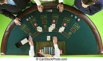 People playing poker at the table, the dealer deals the cards. Green screen. Top view