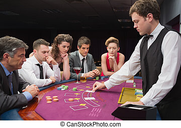 People playing poker - People sitting at table at the casino...