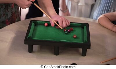People playing table billiard on party