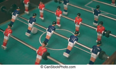 People playing table football game with red and blue...