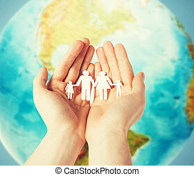 human hands holding paper family over earth globe - people,...
