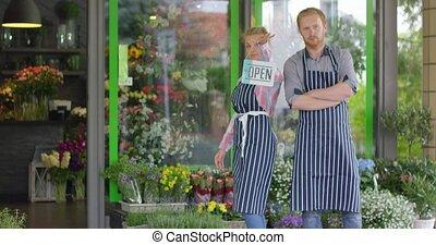 People posing in aprons near shop