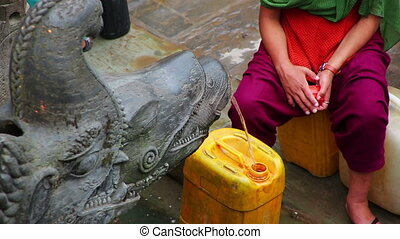 people pouring water container from public fountain -...