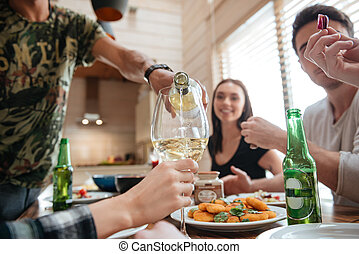 People pouring wine into glass and having dinner with friends