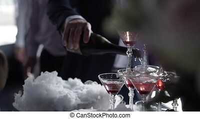 People pouring wine to pyramid of glasses with champagne -...