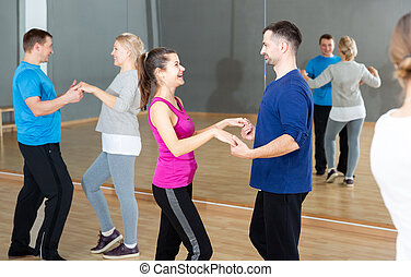 People practicing bachata movements - Smiling dancing people...