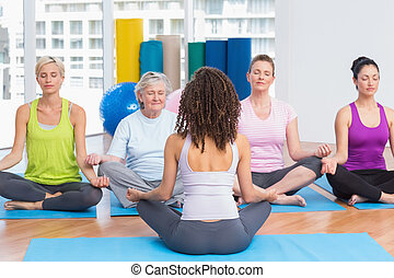 People practicing lotus position in yoga class - Group of...
