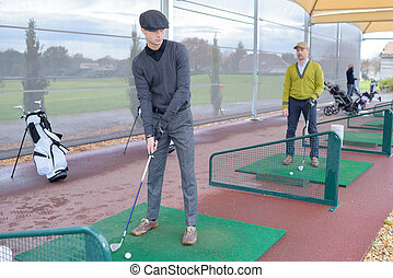 people practise golf at a city centre golf driving range