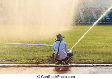 People preparing big sprinkler spray water to grass field in football stadium
