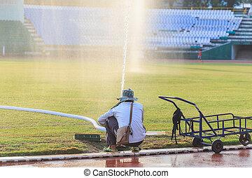 People preparing big sprinkler spray water to grass field in football stadium