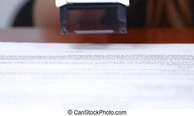 People puts the rectangular stamp on the document. Close up
