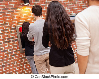 People queuing to withdraw cash at an ATM