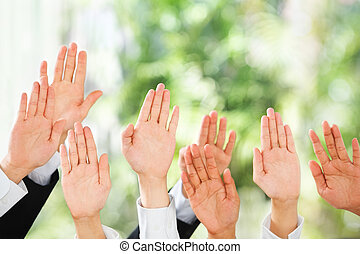 People raise their hands up over green background
