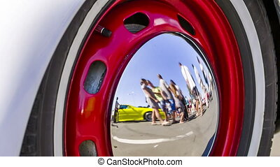 People Reflected In the Hubcap Of Old Car Wheel Disk