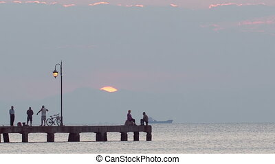 People relaxing on a pier at sunset. Ship is passing by