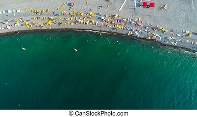 People relaxing on the pebble beach near sea - Aerial drone...
