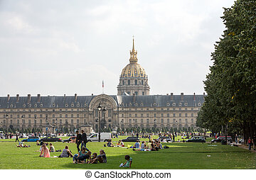 People resting in the park near main entrance Les Invalides....