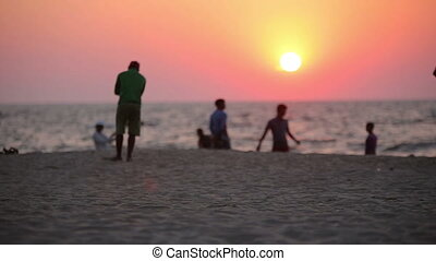 People resting on the beach at sunset