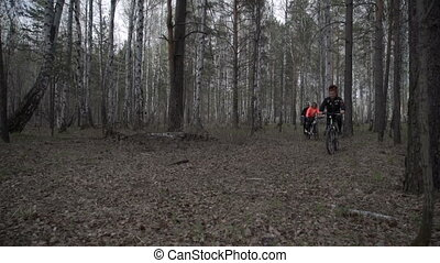 People ride a bicycle in the woods