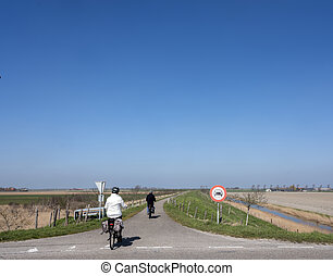 people ride bicycle on sunny spring day in dutch countryside of zeeland