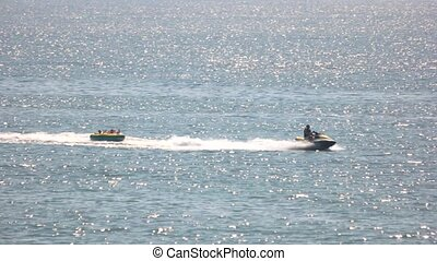 People ride on an inflatable cushion on the sea. Jetski...