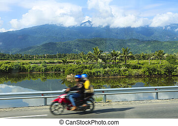 People rides motorcycle on a road in Vietnam