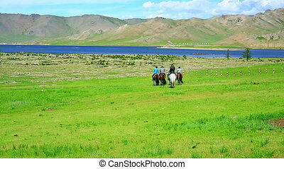 People riding horses in Mongolian landscape, near Terkhiin...